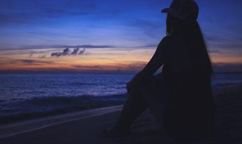 日没後に海を見ながら黄昏ている女性