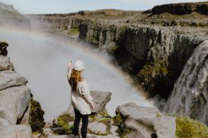 開放的な山頂で虹を見ながら手を伸ばす女性の後ろ姿